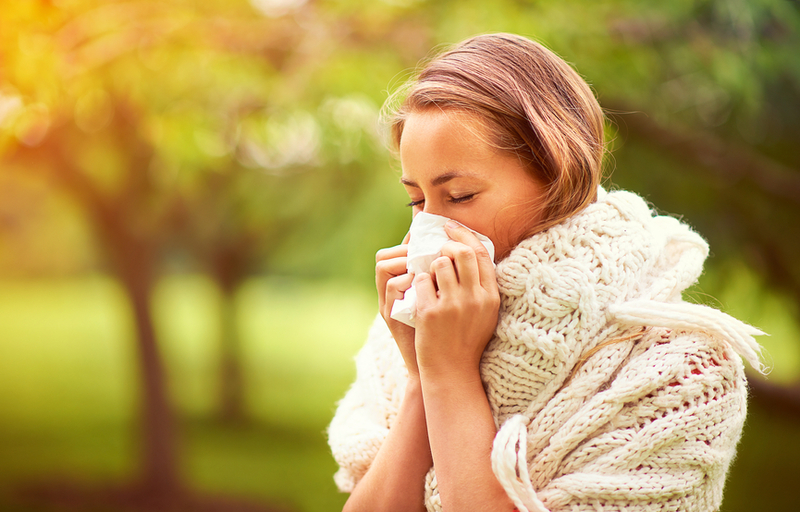 young woman outside in nature suffering with allergies, hayfever, woman blowing her nose