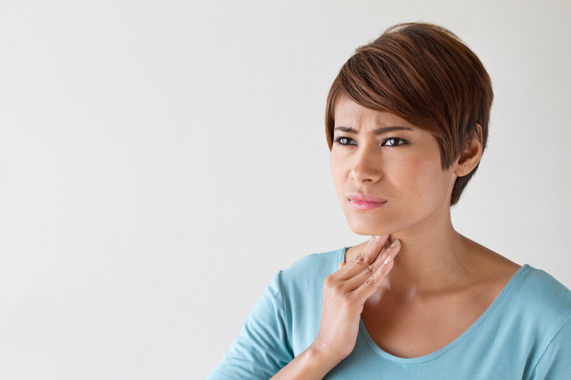 young woman holding her throat, experiencing sore throat