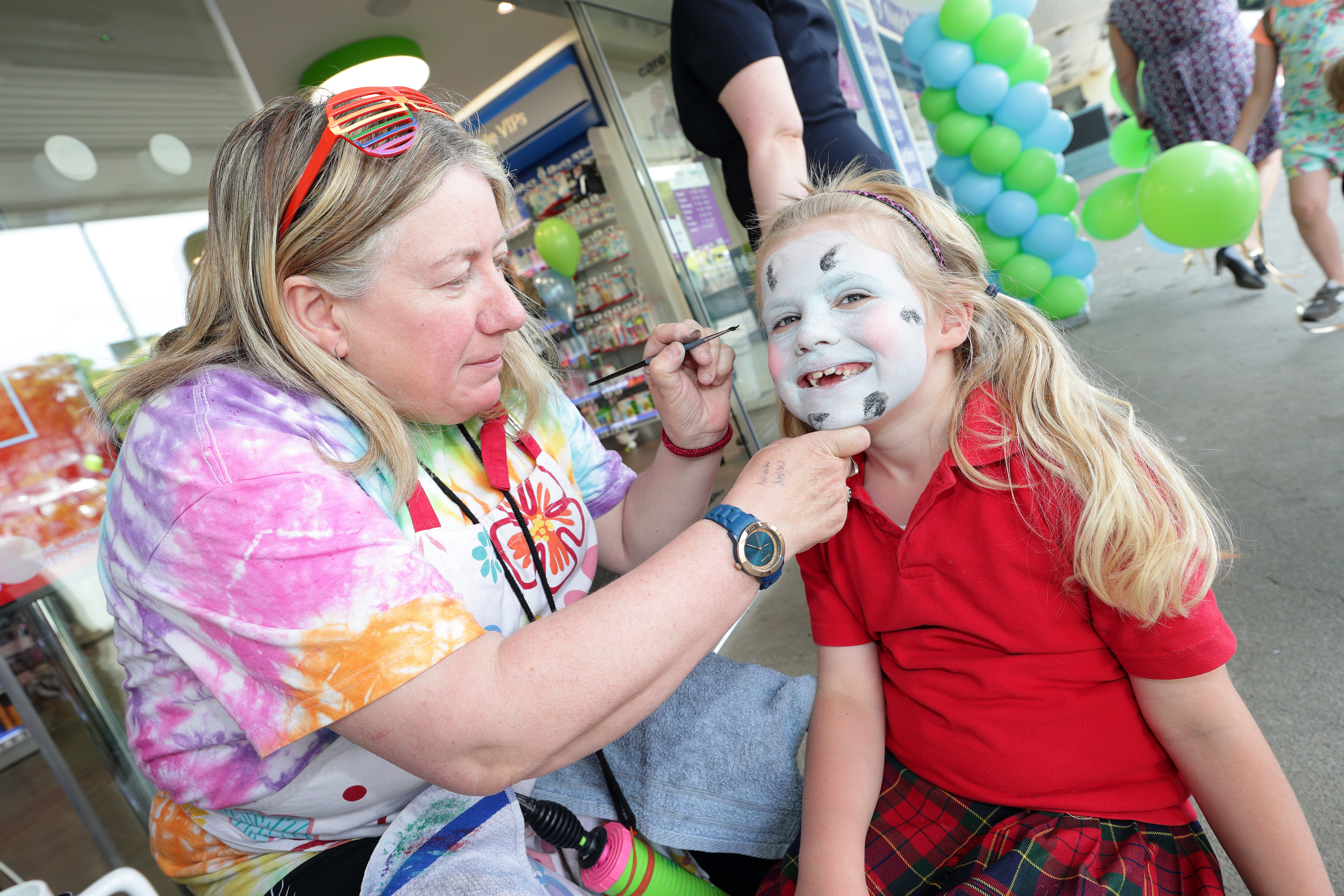 face painter painting young girl's face at Park CarePlus Pharmacy Cabinteely grand opening
