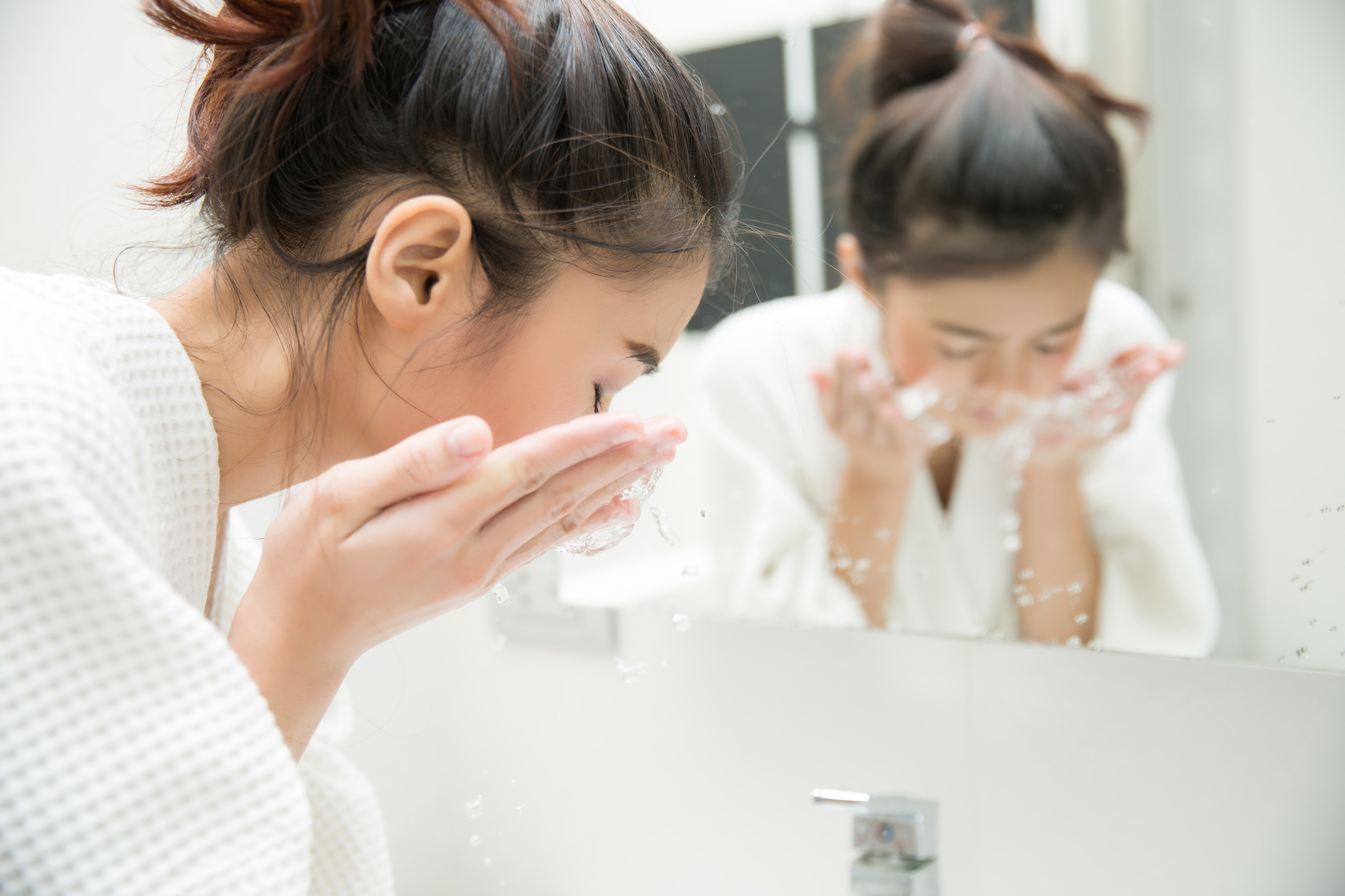 young woman washing her face, acne care, skincare