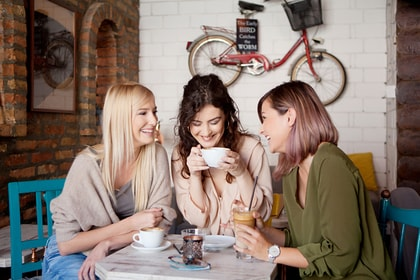 group of women chatting and laughing over coffee, three mothers