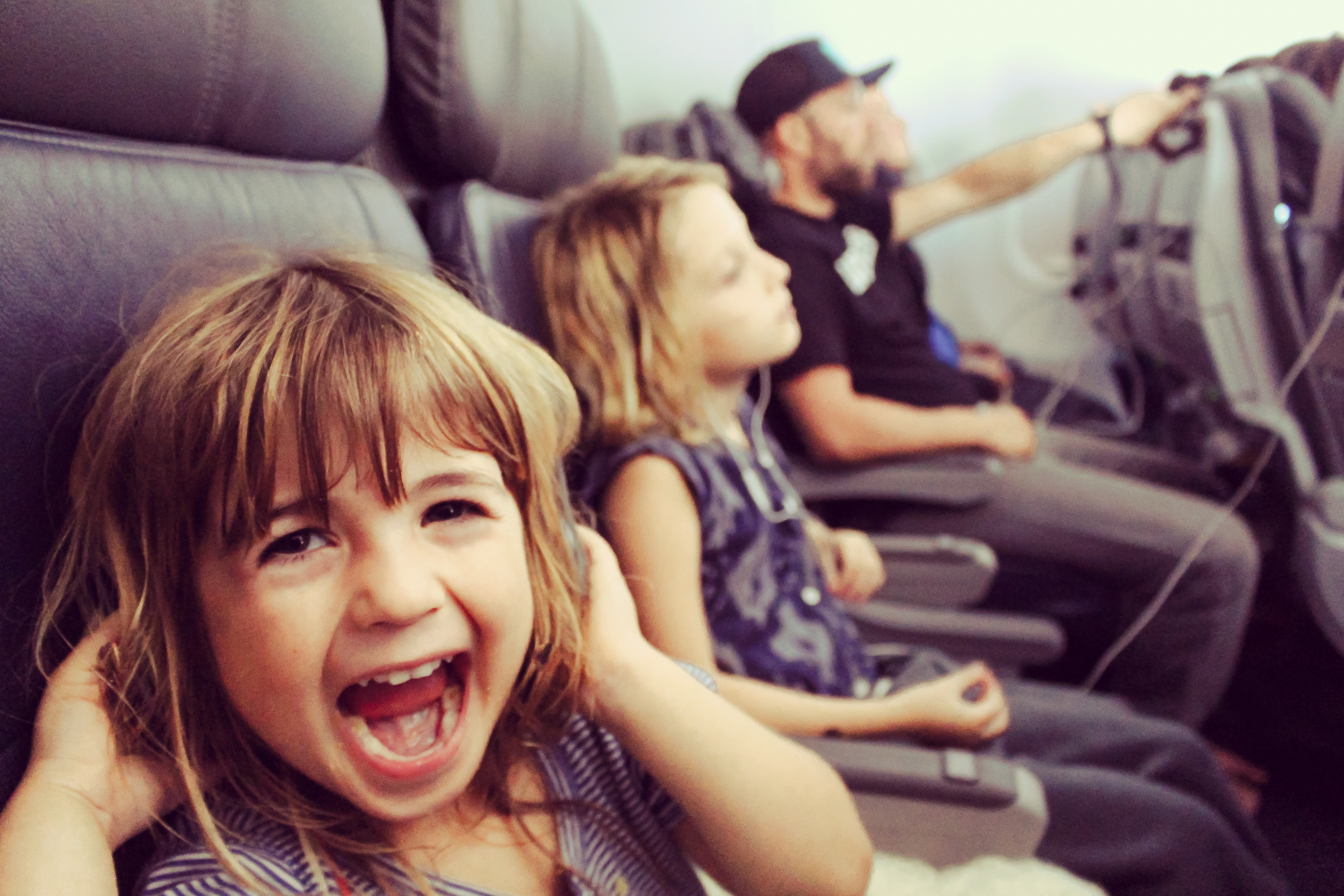 kids on a plane excited to go on holiday