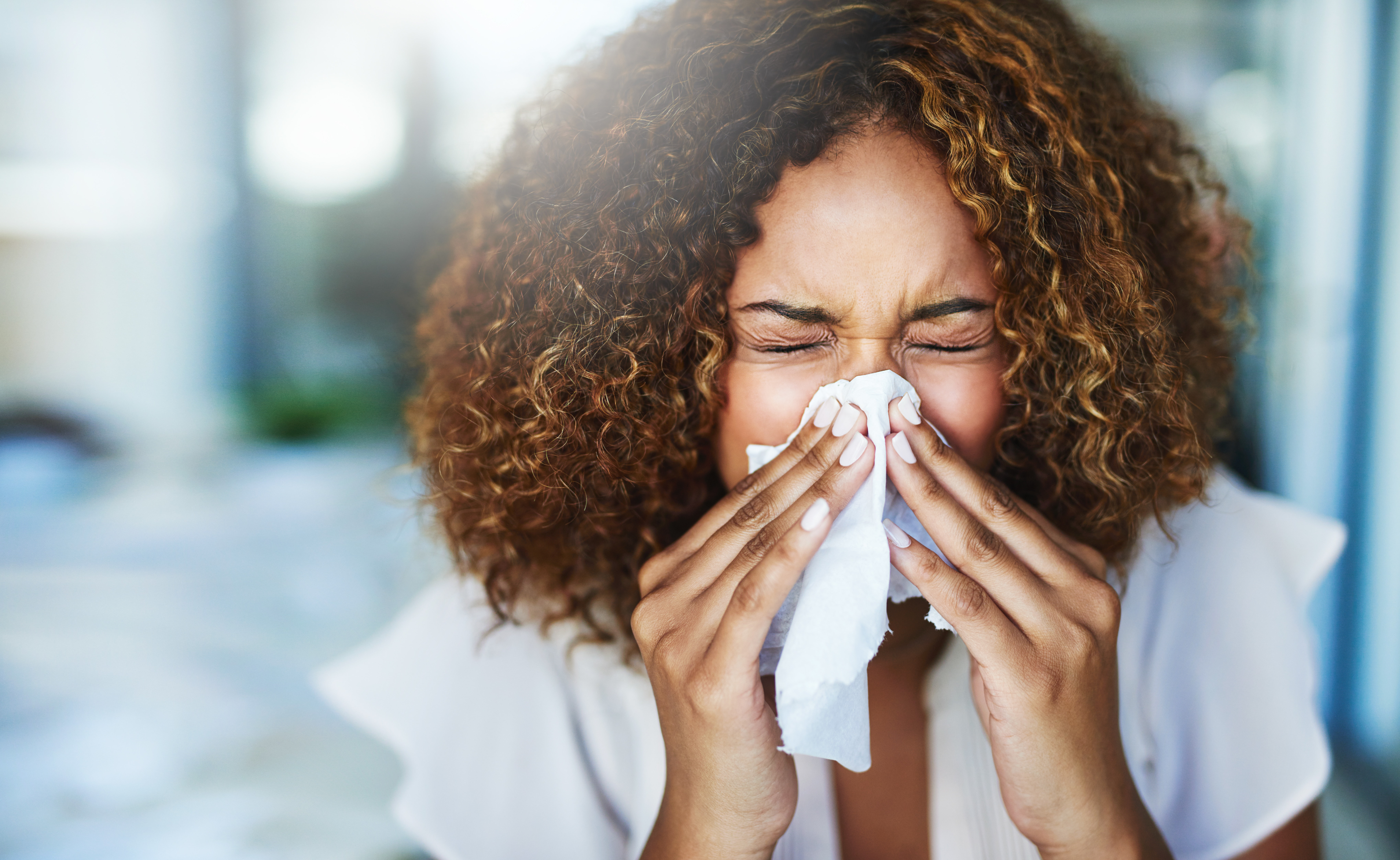 young woman with cold sneezing and blowing her nose