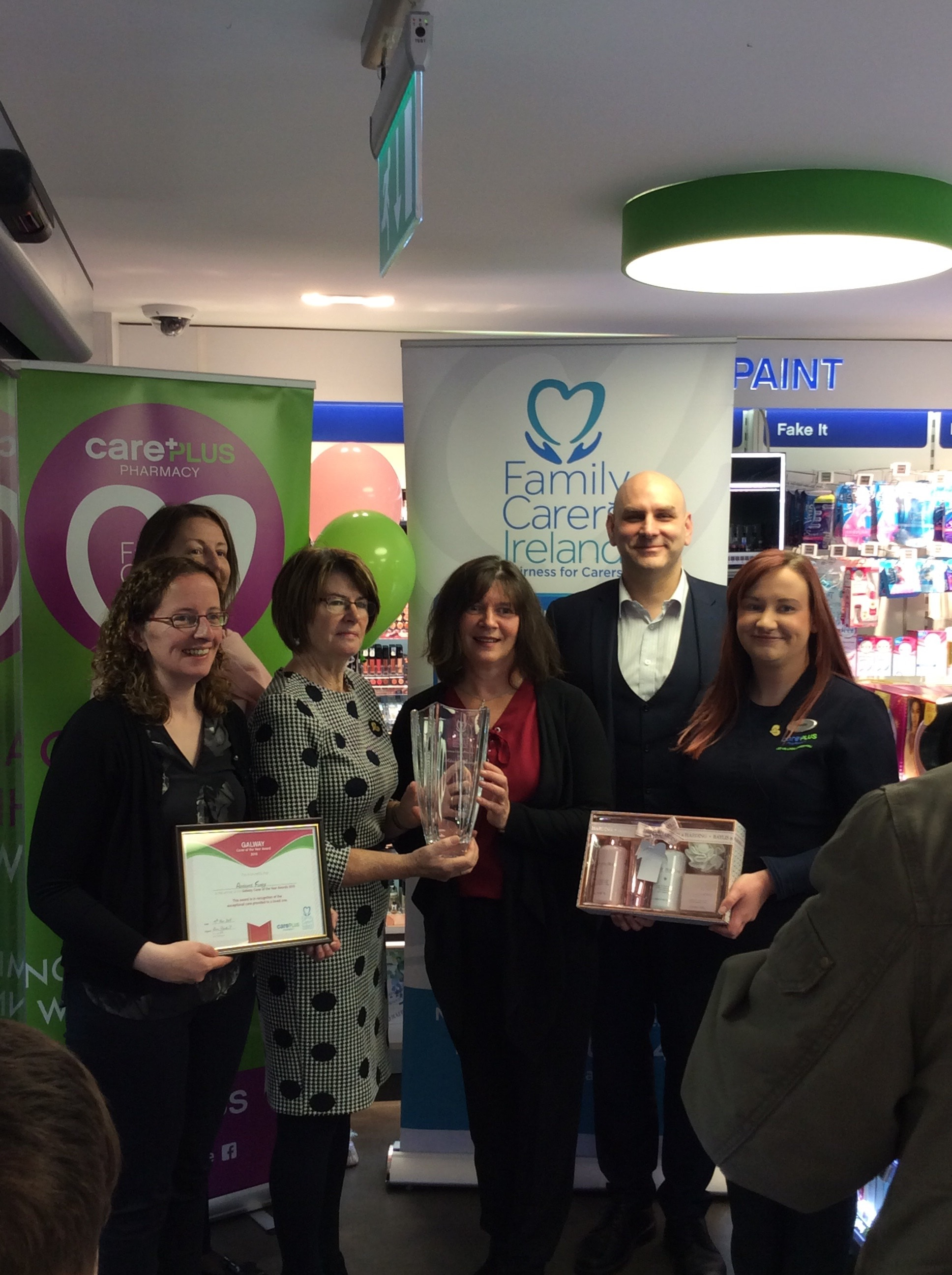 Pharmacist Eoghan Hanley and Staff presenting Adrienne with her award.