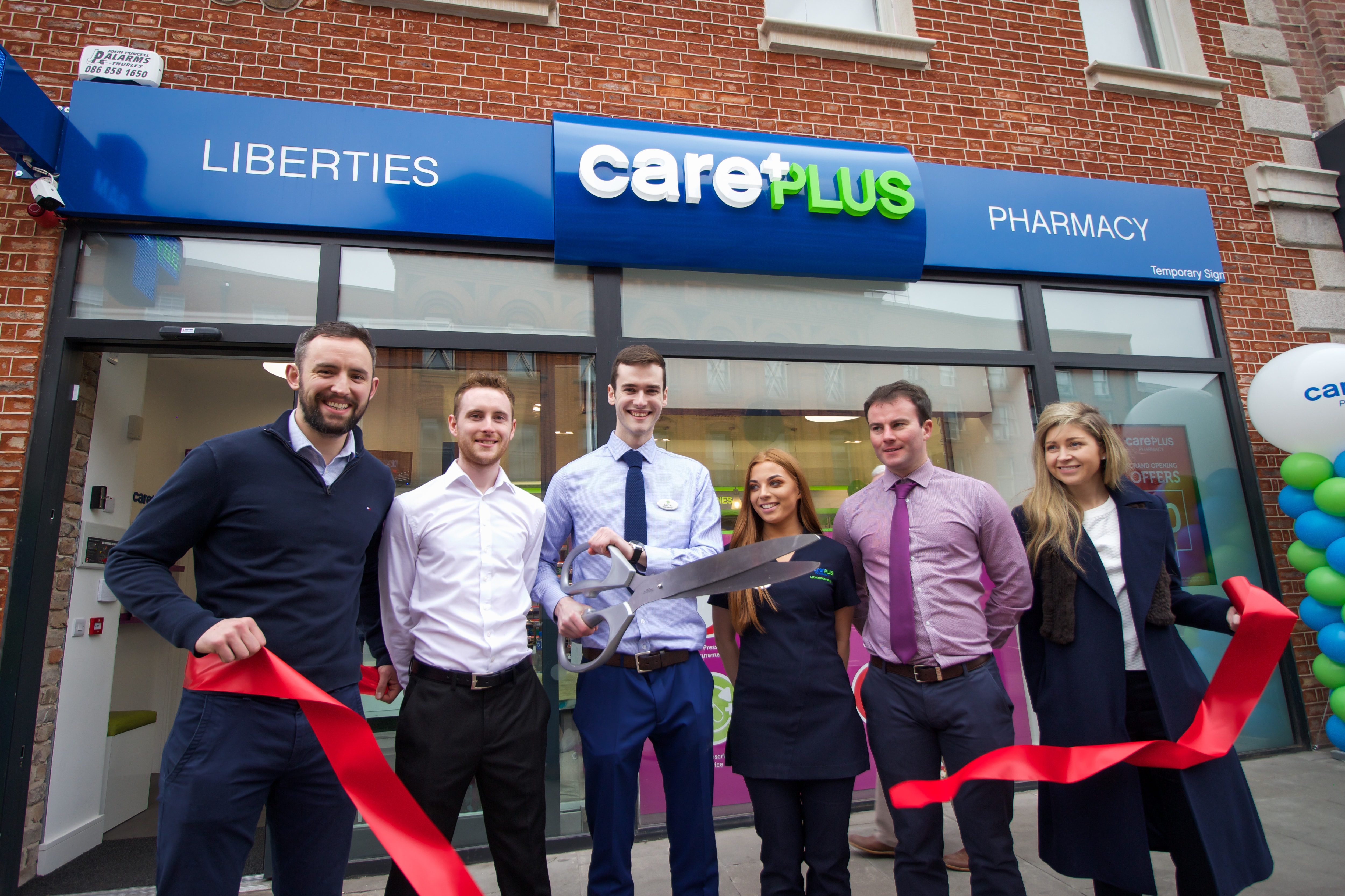ribbon cutting with staff at Liberties CarePlus Pharmacy