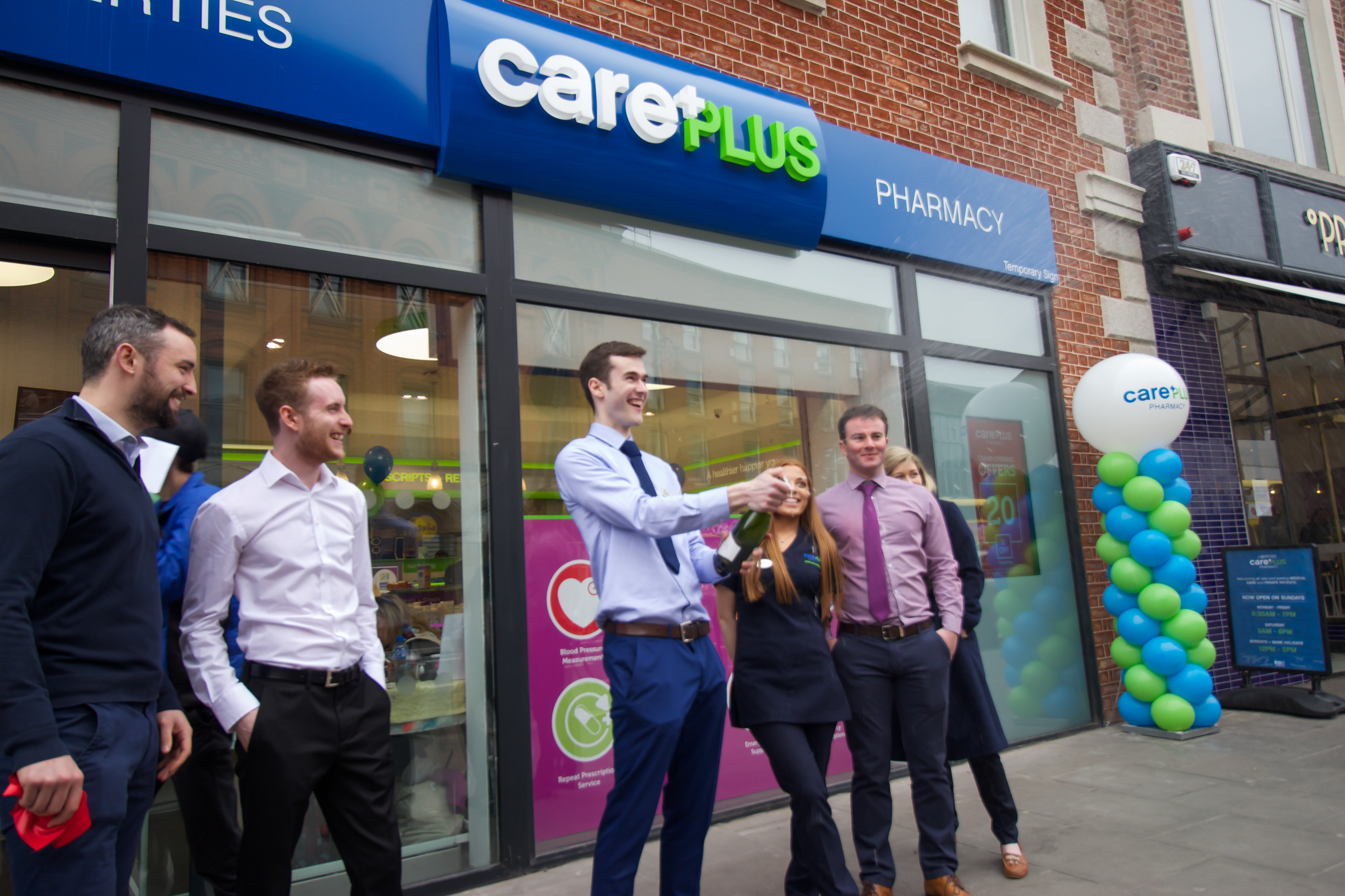 popping champagne outside Liberties CarePlus Pharmacy