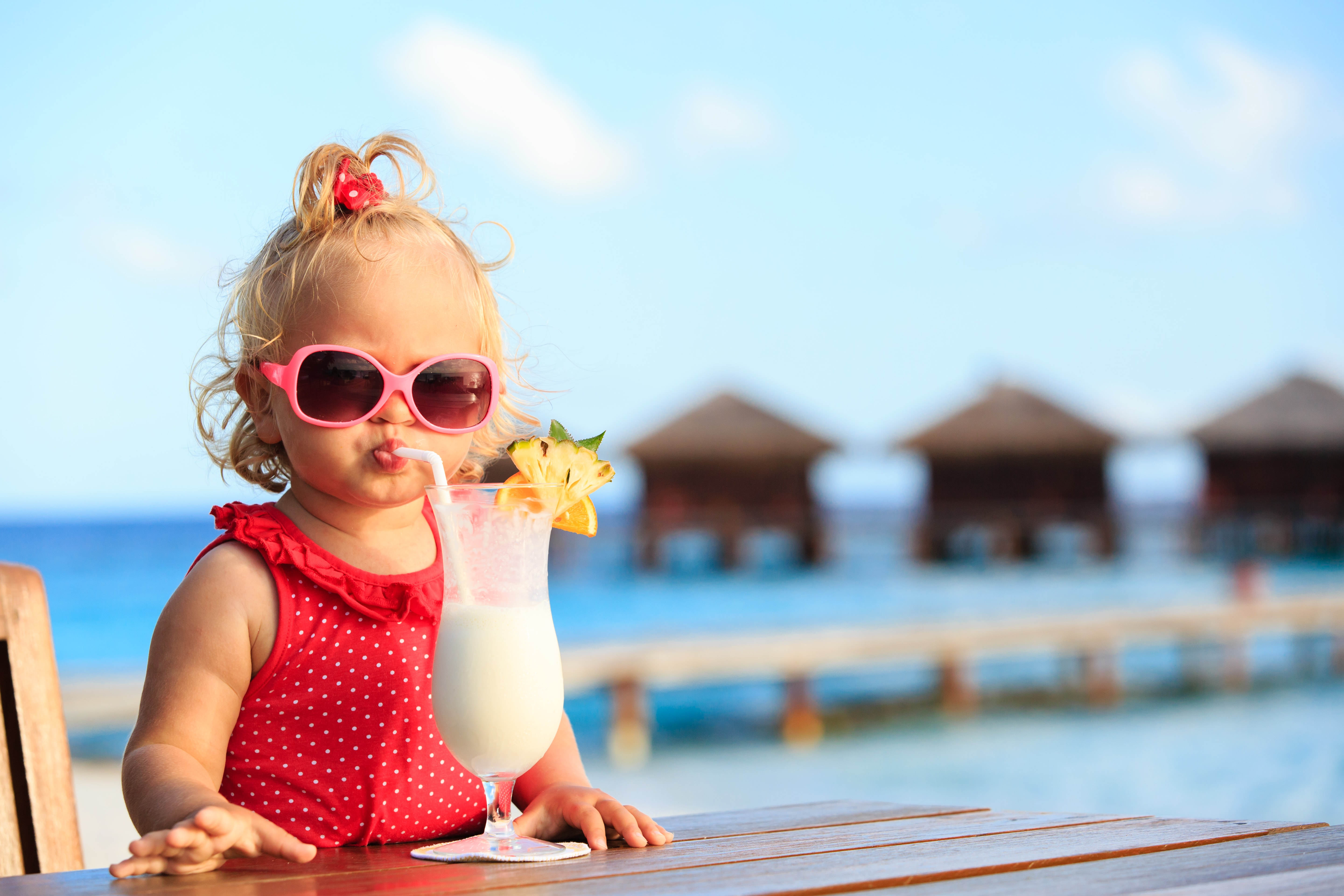 young girl drinking milkshake on holidays, wearing sunglasses and a swimsuit