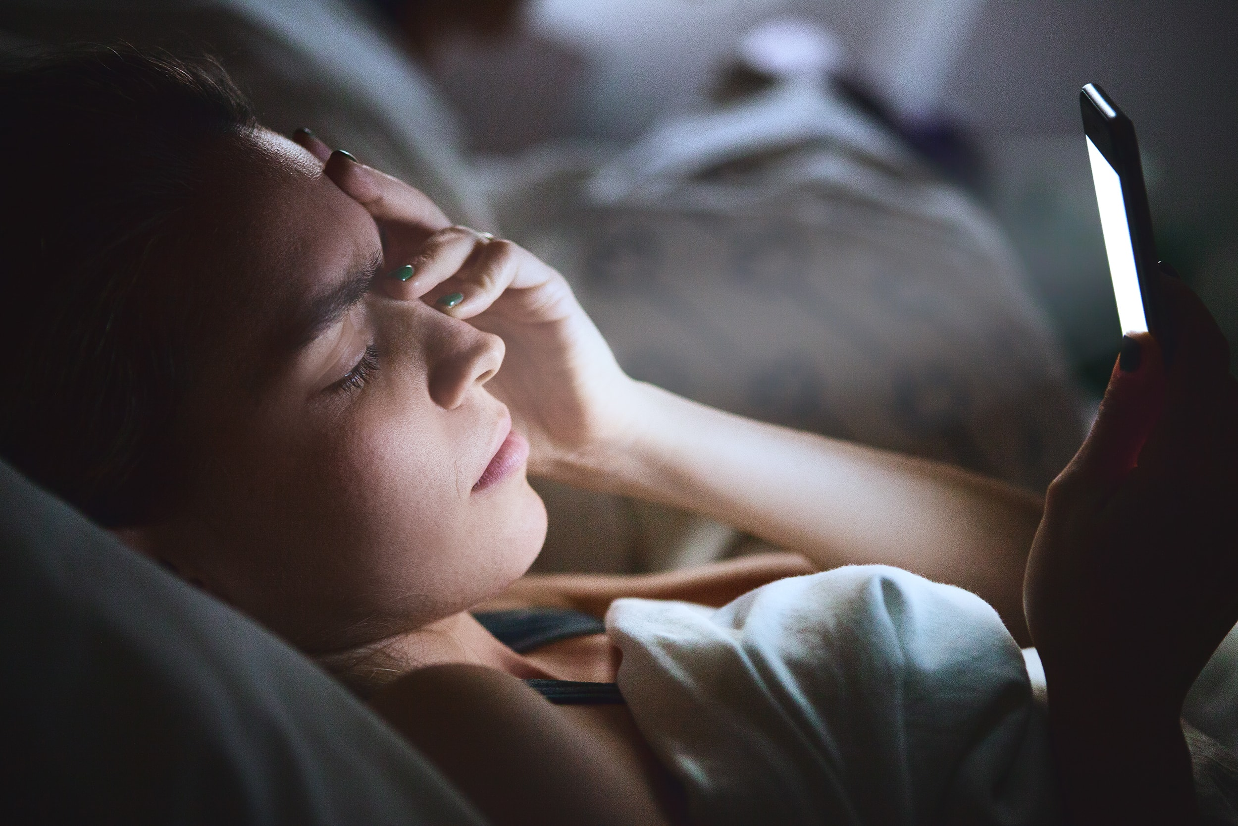 woman in bed looking at her phone unable to sleep