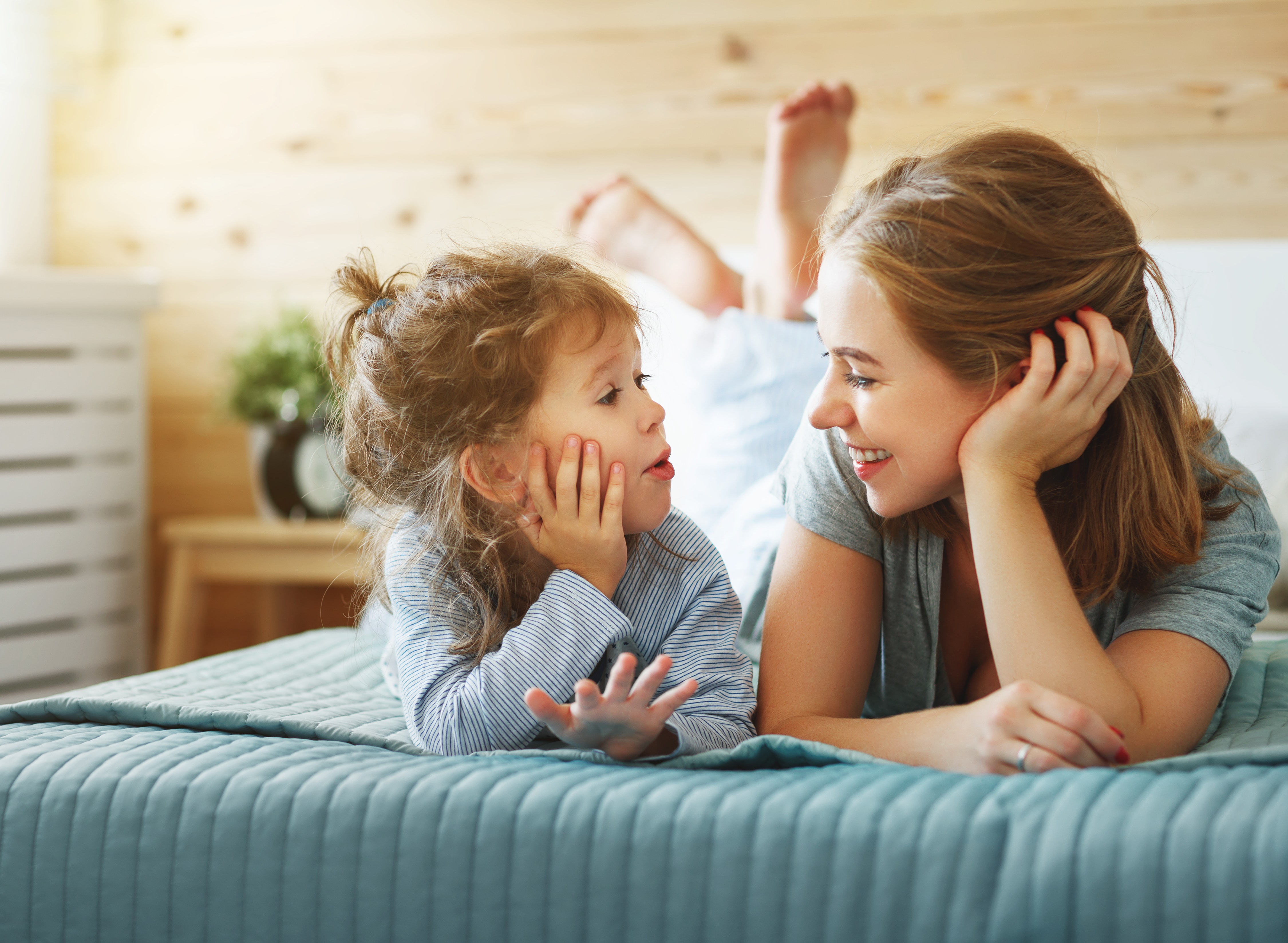mum and young daughter talking and smiling on bed, parenting, balance