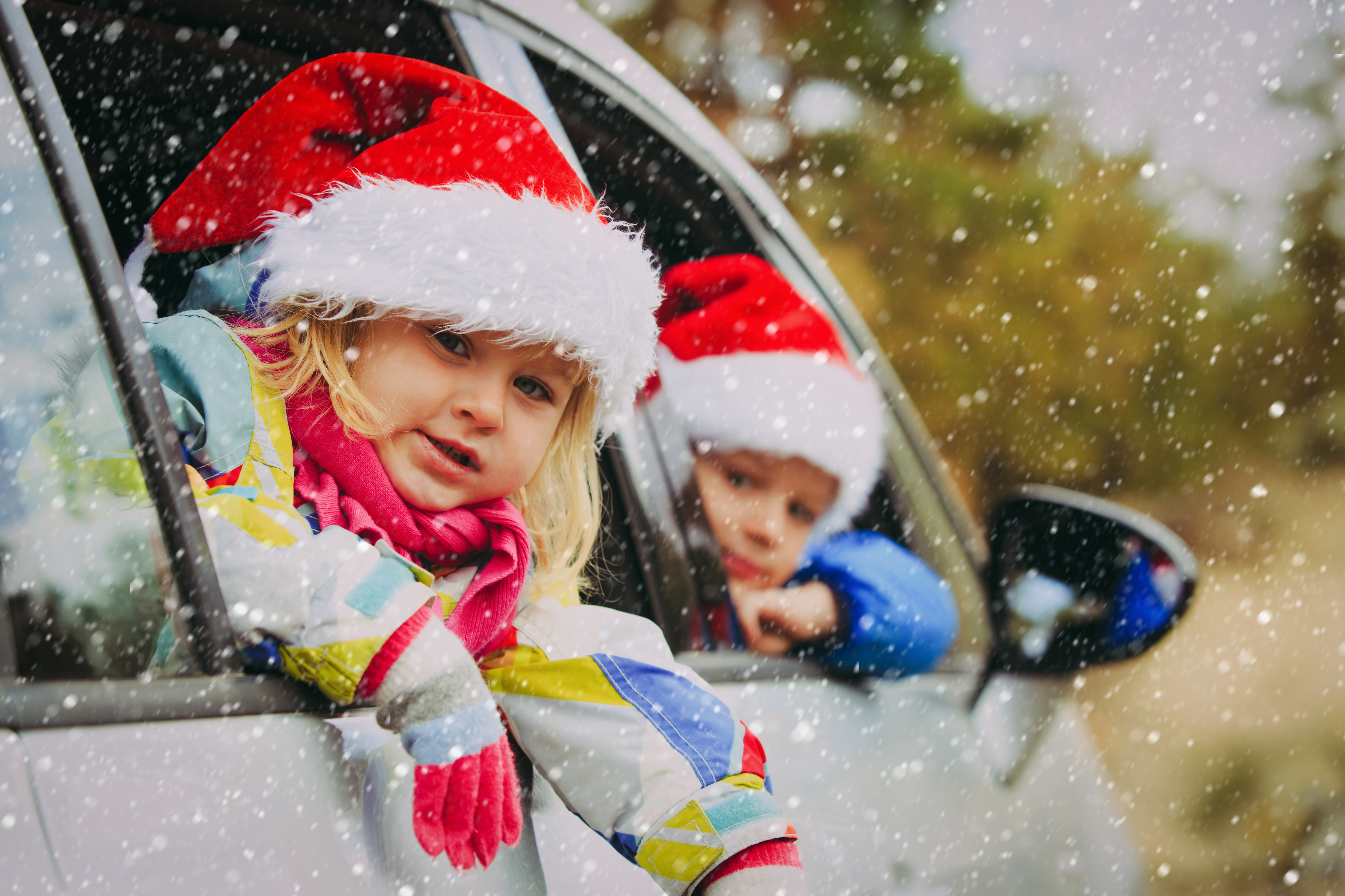 kids at Christmas time, wearing Santa hats leaning out a car window in the snow