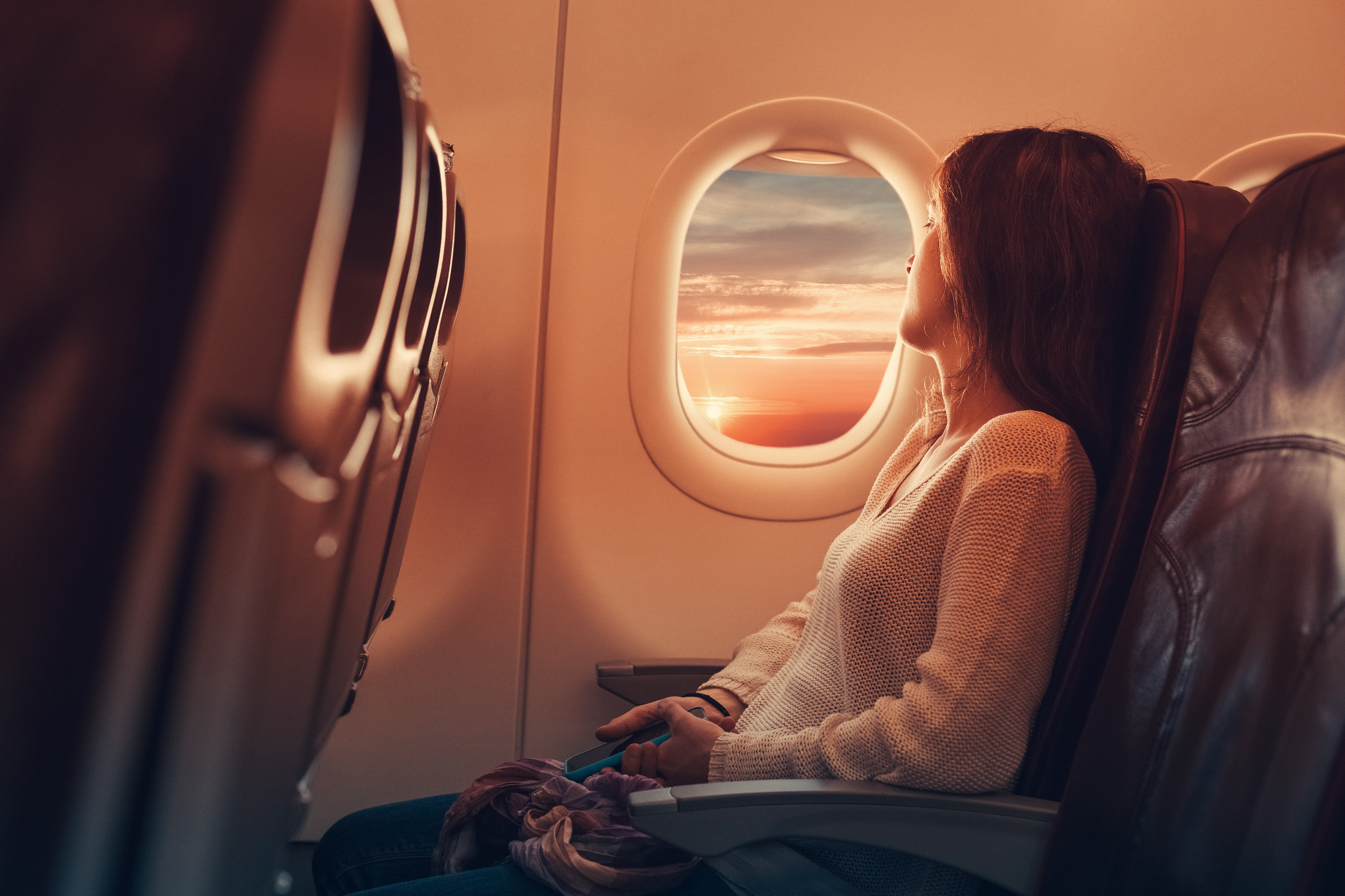 woman looking out airplane window flying